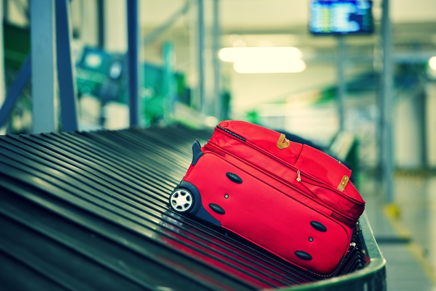 avoid allergies while on vacation - red suitcase in airport baggage claim