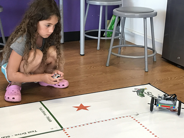 STEM learning and summer fun - girl working with a robot