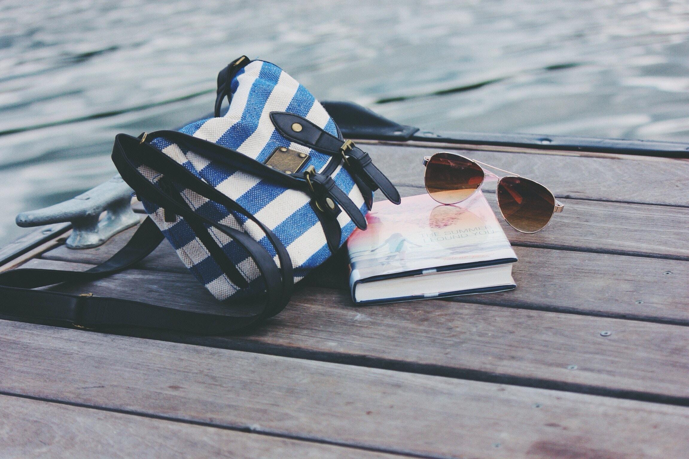 bag, book, sunglasses on a pier